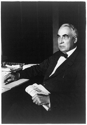 Warren G. Harding, seated at desk, wearing bow...