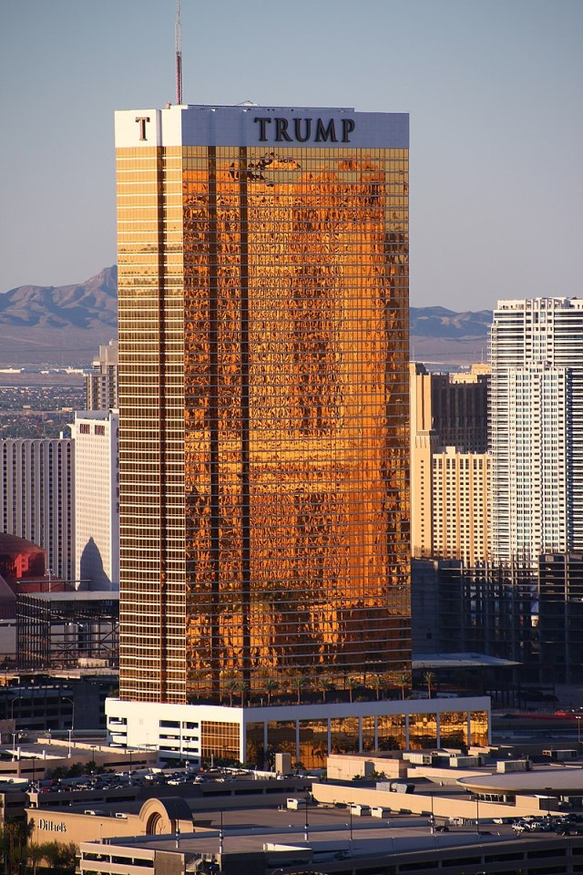 A tall rectangular-shaped tower in Las Vegas with exterior windows reflecting a golden hue. It is a sunny day and the building is higher than many of the surrounding buildings, also towers. There are mountains in the background. This tower is called the Trump Hotel Las Vegas.