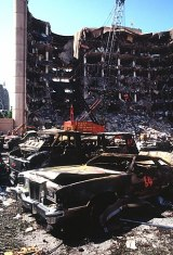 A view of the destroyed Alfred P. Murrah Federal Building, two days after the bombing, burned out automobiles in the foreground.