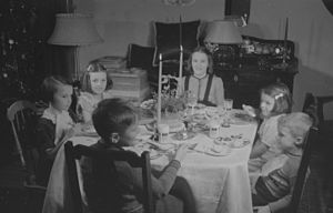 English: A group of children at Christmas dinner.