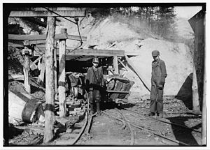 English: Boys move coal cars at the entrance t...