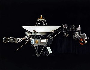 A space probe with squat cylindrical body topped by a large parabolic radio antenna dish pointing upwards, a three-element radioisotope thermoelectric generator on a boom extending left, and scientific instruments on a boom extending right. A golden disk is fixed to the body.