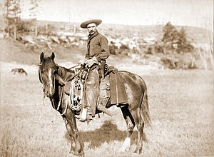 Photograph shows side view of a cowboy on a ho...