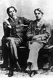 Two men sit on a bench with their legs crossed. Both are well dressed in suits.