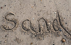 """The word """"sand"""" written in sand"""