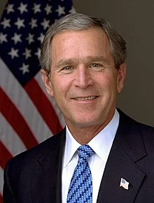 A portrait shot of a smiling older male looking straight ahead. He has short gray hair, and is wearing a dark navy blazer with a blue styled tie over a white collared shirt. In the background is an American flag hanging from a flagpole.