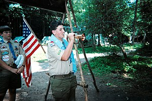 A Scout assembles his troop at a summer camp.