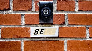Doorbell button on brick with label