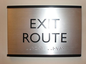 Exit route sign with braille at an office buil...