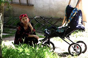 A woman from Tajikistan with a baby stroller i...