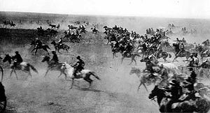A black-and-white photograph of cowboys on their horses