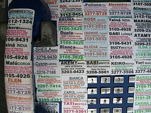 Stickers on a pay phone advertising the servic...