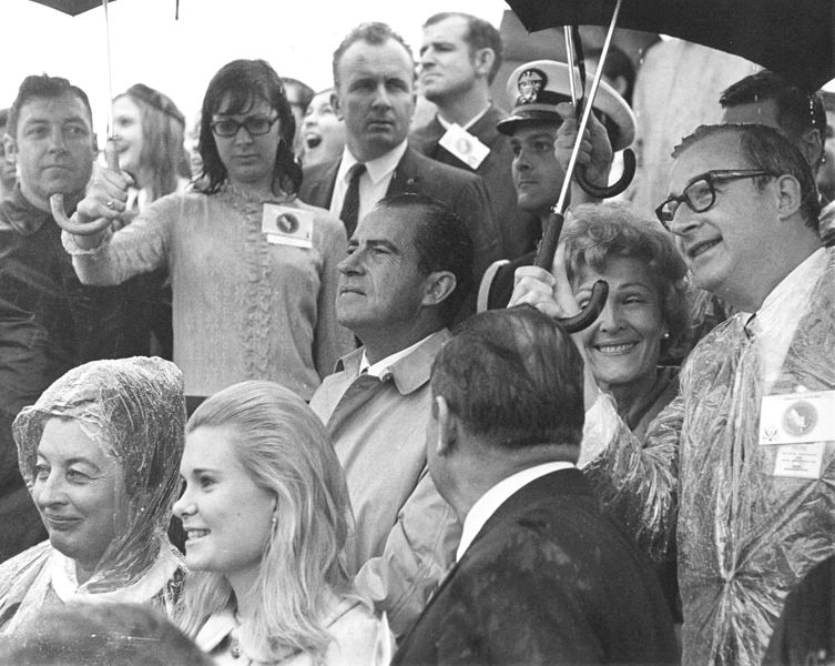 NASA Administrator Dr. Thomas Paine holding umbrella for Nixon