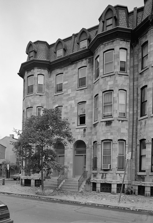 End section of a four-story stone terraced building. Two adjacent doors are at center, each with a short flight of stairs leading up from the street to the first level. Either side of the doors, at left and right, the building has two rounded tower-like sections, each with nine large sash windows (three on each level). Four more large windows are at center, above the doors. The uppermost (attic) level has four smaller windows protruding from the roof with architectural feature. At street level, grilled skylights illuminate basement rooms.