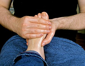 Photograph of a man massaging a woman's foot u...