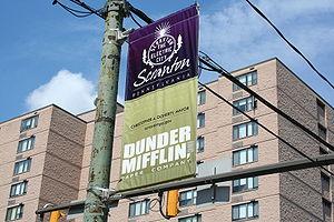 A banner promoting Dunder-Mifflin, the fiction...