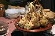 Unopened bunch of cooked ketupat in a plate