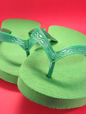 green plastic flip flops against colored backg...