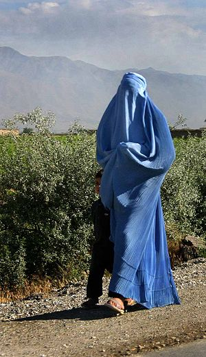 A woman with burqa on walking by the road in n...