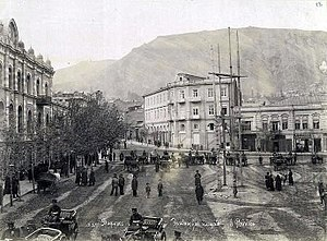A picture of a city square with people walking about and people riding in carriages