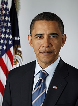 A portrait shot of a serious looking middle-aged African-American male looking straight ahead. He has short black hair, and is wearing a dark navy blazer with a blue striped tie over a light blue collared shirt. In the background are two flags hanging from separate flagpoles. An American flag, and one from the Executive Office of the President.