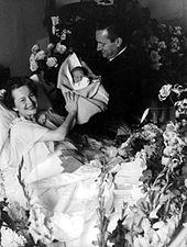 Sonriendo mientras sostiene a su hijo recién nacido con su esposo