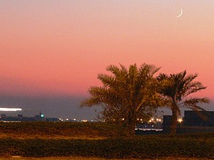 A crecent moon can be seen over palm trees at ...