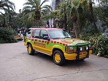 A utility car painted in green, yellow and red colors in a jungle park environment.