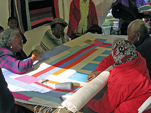English: Women from Gee's Bend work on a quilt...