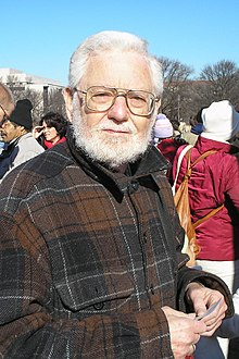 picture of a gray-haired man wearing glasses and a brown plaid flannel shirt; behind him is a crowd of people