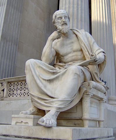 A photograph of a white stone statue in the classical Greek style of a man wearing a toga, holding a scroll, who seems to be deep in thought. In the background are steps leading up to a building with classical Greek pillars, all carved of the same white stone.
