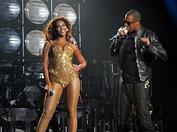 A woman stands next to a man who is performing using a microphone