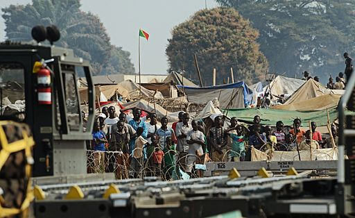 Refugees of the fighting in the Central African Republic observe Rwandan soldiers being dropped off at Bangui M'Poko International Airport in the Central African Republic Jan. 19, 2014 140119-F-RN211-760