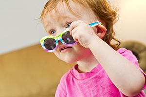 English: A young girl peering over her sunglasses.