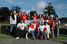 A group of thirteen supporters pose together, some wearing rugby jerseys while others sport traditional Japanese costumes and Japanese flags.