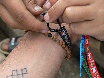 Original caption: Ne ties a friendship bracele...