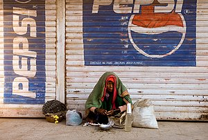 A woman waking up on a sidewalk in Bijapur, In...
