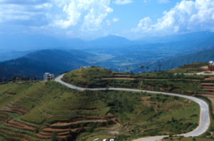 Narrow winding road leads through extremely di...