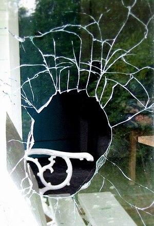 English: Broken window in a vandalised cottage...