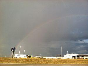 English: A faint rainbow with rain in the back...