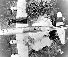 Black and white photo of a four engined World War II-era aircraft being viewed from above while it is flying over a city. A large cloud of smoke is visible immediately below the aircraft.