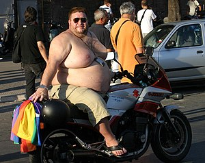 An obese topless man on a motorcycle. Original...