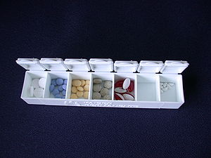 A pill box with various medications in it.