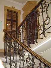 Ornate staircase, a landing with an interior door and window, staircase continuing up