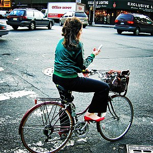 A woman reading SMS messages on her mobile pho...