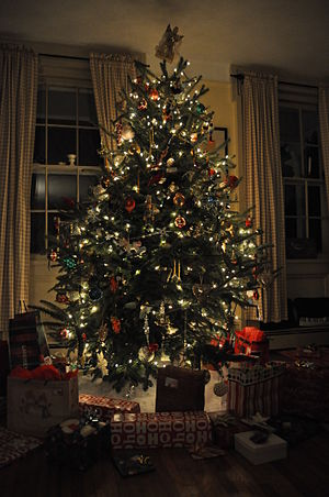 English: A Christmas tree lit and decorated, s...