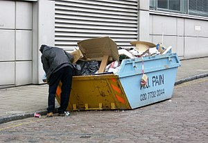 A man rummaging through a skip at the back of ...