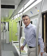 Macri walking into a new, colorful subway car