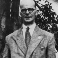Upper torso of balding, bespectacled man wearing suit with tie