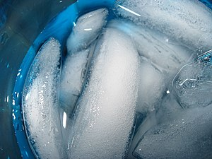A photo of a cup of ice water taken from above.
